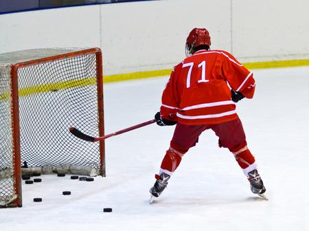 heed: hockey player near the ice hockey net