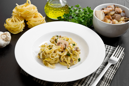 pasta sauce: tagliatelle and mushrooms with fresh ingredients  on black wood