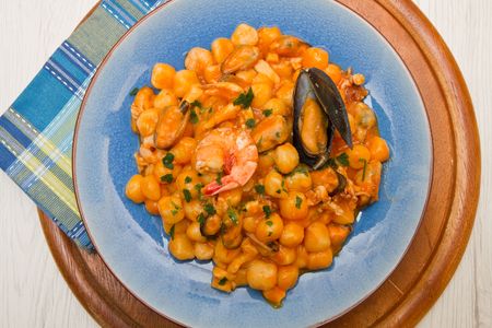 sauce dish: blue dish with gnocchi,seafood and tomatoes sauce Stock Photo