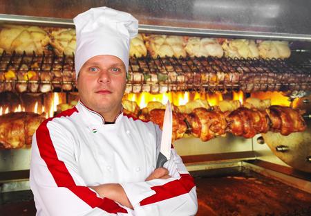 pollo rostizado: cocinero frente a los pollos a la brasa