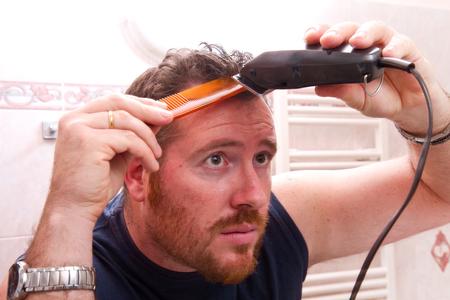 electric razor: man grooming his hair with electric razor