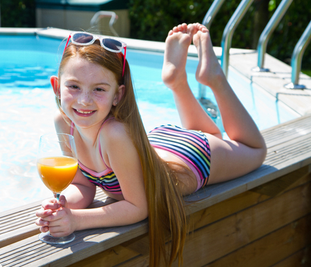 Smiling little red girl with cocktail in the swimming pool Stock Photo