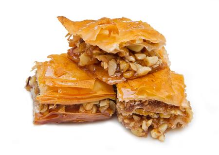 picada: Pedazo de dulces baklava en el fondo blanco
