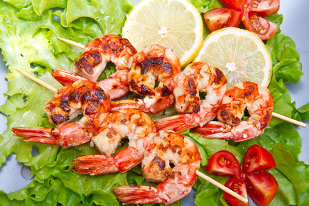 dieta: plate of grilled prawns with salad and cherry tomatoes