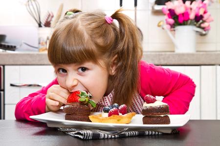 comiendo frutas: niña de preparar y comer la torta de frutas Foto de archivo