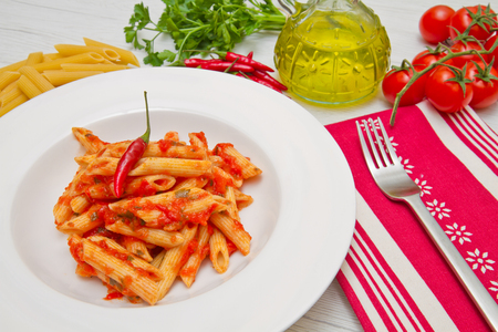 sauce dish: dish with penne and arrabbiata sauce on white wood