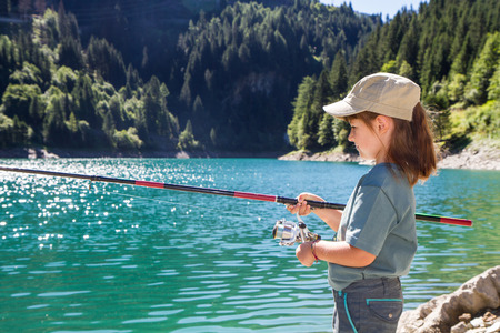 pelvis: young girl fishing in a lake in the mountains