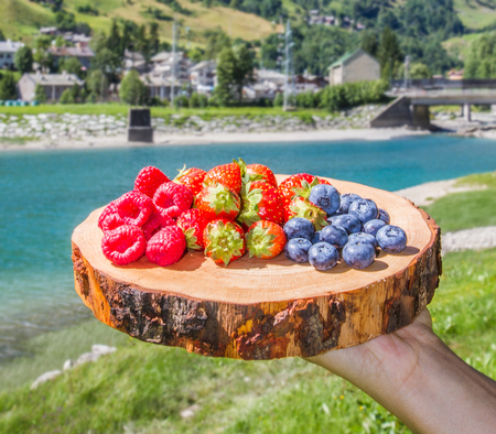fresh berries on wooden cutting board with background mountains