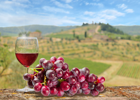 glass of red wine with bunch of grapes with the Tuscany as background