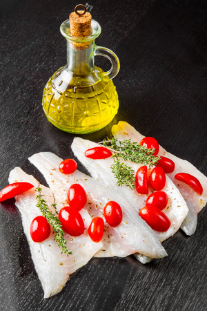 Raw sea bass fillets with cherry tomatoes on black wood Stock Photo