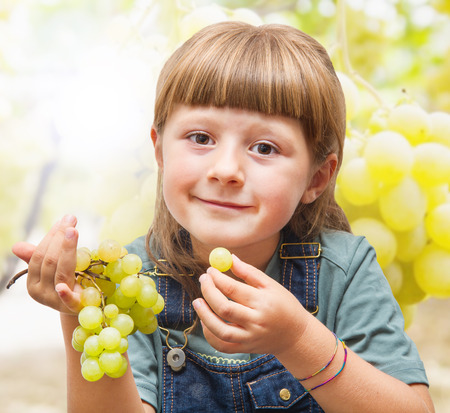 eating fruits: Girl eating grapes in the vineyards Stock Photo