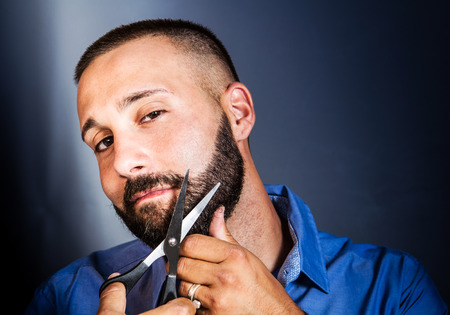 man with beard: young man settles his beard with scissors