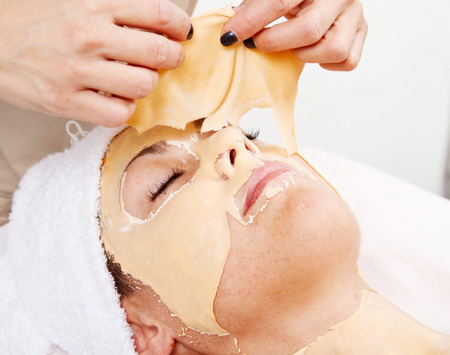 Beautiful young woman remove  facial mask  in a beauty center photo