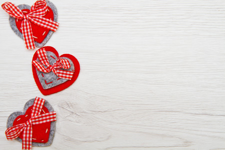 valentines background: Valentines day background with handmade toy hearts over wooden table