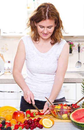 ifestyle: Happy young housewife making fruits salad Stock Photo