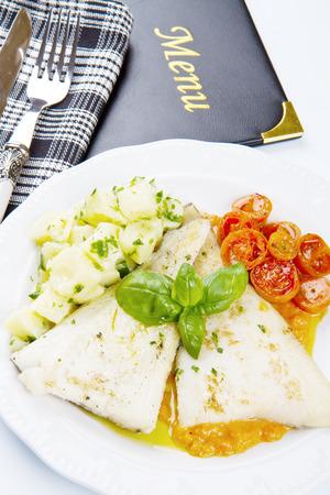 sauce dish: white dish of Fresh black cod with potatoes and tomatoes sauce Stock Photo