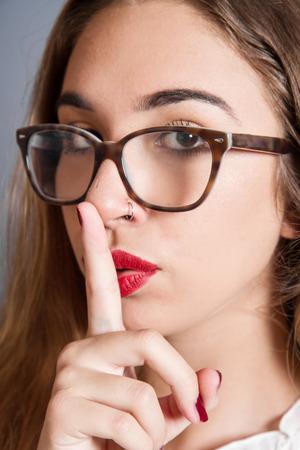 guardar silencio: chica morena con un dedo en sus labios muestran a guardar silencio, silencio.