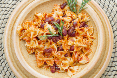 vegetarian cuisine: earthenware pot with Italian pasta with red kidney beans