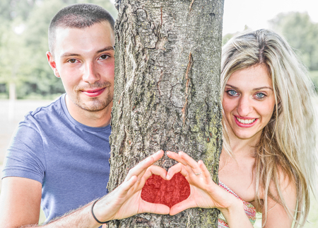 engaged: engaged couple at the park that make the heart symbol