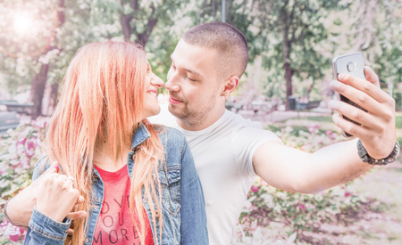 couples hug: young couple with cellphone at the park