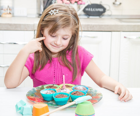 Cute little girl blowing out candles on birthday muffin at home Stock Photo