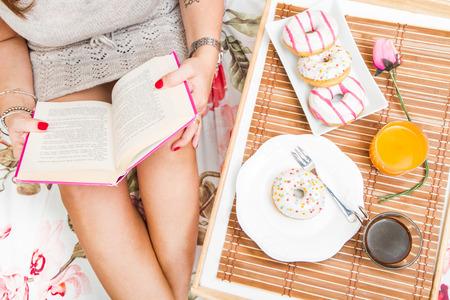 Frau mit Frühstück im Bett, während ein Buch zu lesen