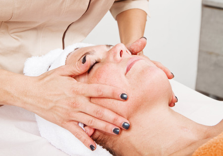 Beautiful young woman receiving facial massage with closed eyes in a beauty center photo