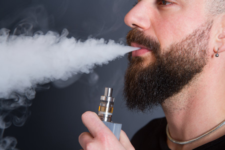 man with beard: beared man  smoking electronic cigarette