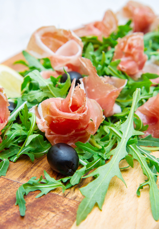 rocket lettuce: chopping board with aragula and raw ham Stock Photo