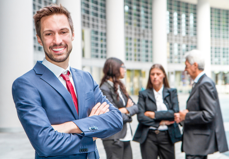 collegue: Beautiful man on the background of business people