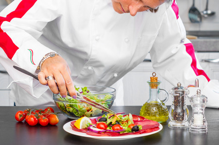 rofessional cook prepares a plate with salami and fresh salad  Stock Photo