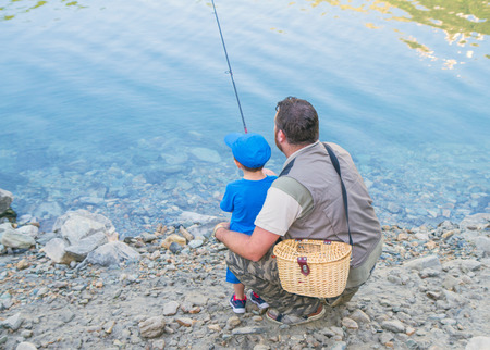 Dad and daughter are fishing together in a lake in the mountains photo