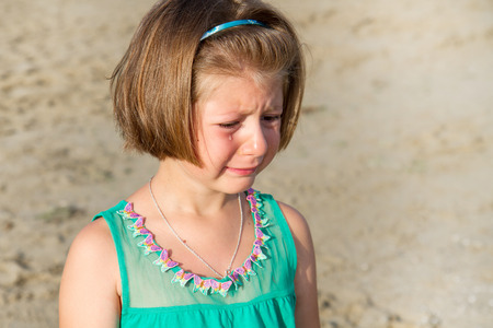 punishing: Little girl crying at the beach