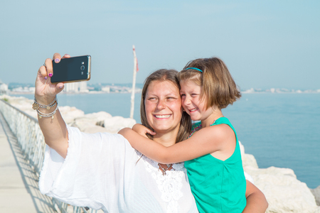 Mom and daughter are taking a picture smiling photo