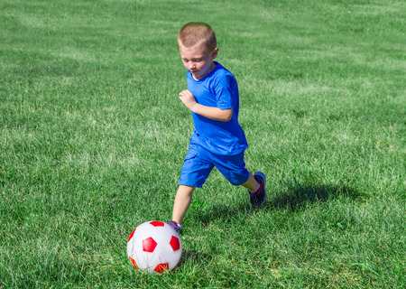 Baby playing football in the meadow photo