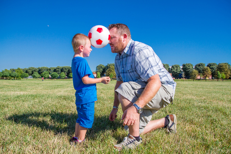 Dad and son play together with the ball photo