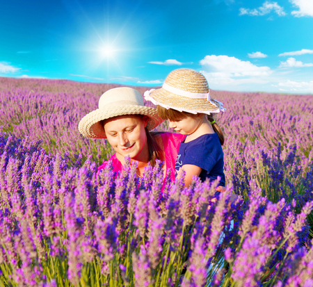 Happy little girl with her mother are in a lavender field photo