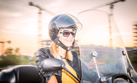Young woman riding scooter in the city. Portrait of a beautiful woman with a moped