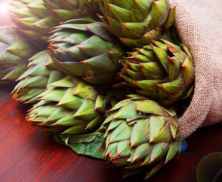 artichoke in burlap sack on wood Standard-Bild