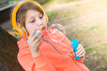 young girl listening music with headphone is blowing soap bubble 版權商用圖片