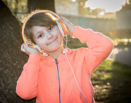 young girl is listen music with headphone to the park 版權商用圖片