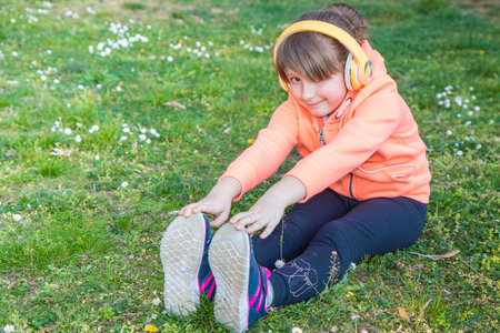 young girl is doing exercises at the park listen music