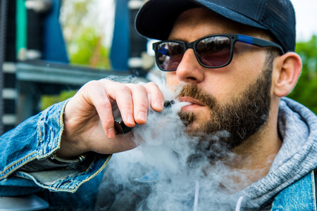 man with a beard smokes an electronic cigarette