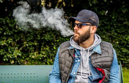 man with a beard smokes an electronic cigarette sit on a bench Фото со стока