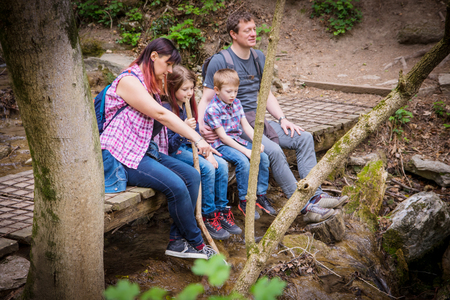happy family are sitting on a wooden bridge in the middle of forest Reklamní fotografie