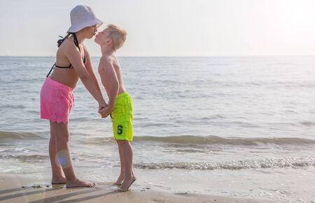 Hermano y hermana, besos en la playa en un buen día de verano Foto de archivo
