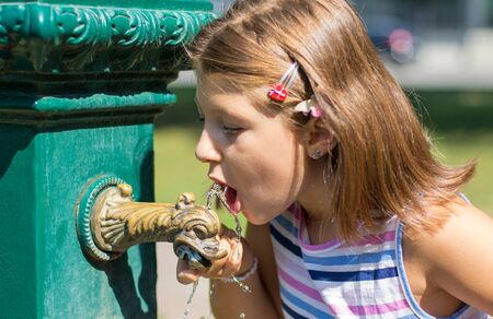Young girl drinking from a water fountain at the park