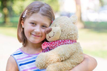 Little girl  holding large teddy bear outside