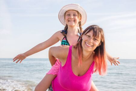 Smiling mother and beautiful daughter having fun on the beach. Portrait of happy woman giving a piggyback ride to her girl