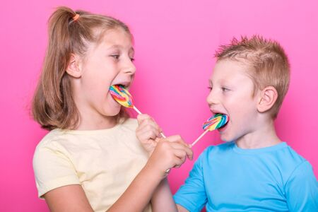Happy smiling children with sweet lollipop having fun over colorful pink background 版權商用圖片